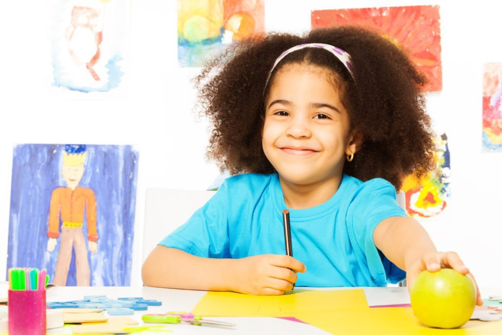 Smiling African girl at the desk holds pencil take apple while sitting in playroom with wall behind which is full of kids drawings